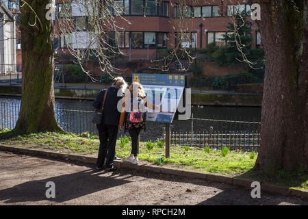 Visitors look at an information panel on Abbey Wharf  by The River  Kennet in Reading. - Stock Image