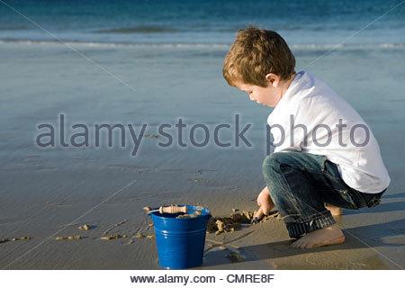 Boy digging sand - Stock Image