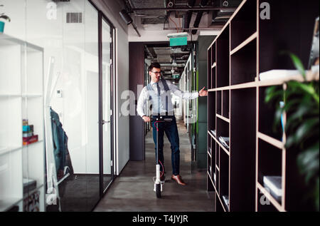 Young businessman with motor scooter in an office building, taking a break. - Stock Image