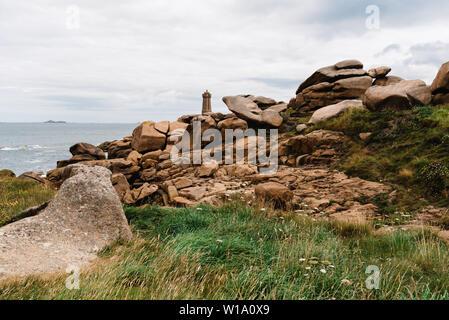Ploumanac'h lighthouse against sky. Rocky coast landscape - Stock Image