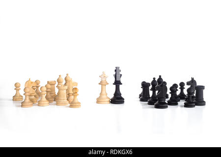 White queen and black king, traditionally confronted in chess game, are together. Image in isolated white background. - Stock Image
