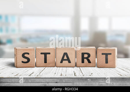 Start sign in a bright office on a wooden table with white worn planks - Stock Image