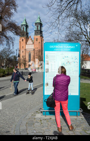Woman reading the information board outside the cathedral on Ostrow Tumski Island,  in the Polish city of Poznan Poland - Stock Image