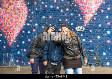 Tourists having fun taking a selfie in front of a large painted mural on a wall in a street in London. - Stock Image