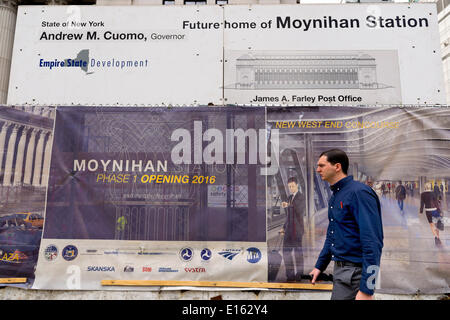 Manhattan, New York, U.S. - May 21, 2014 - Pedestrian walks past construction sign on 8th Avenue at the James A Farley Post Office, which is the future home of Moynihan Station, in midtown Manhattan. Signs show new West End Concourse and this Empire State Development project is scheduled for a Phase 1 Opening 2016. - Stock Image
