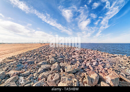 Wide angle sea coast industrial landscape with skyline, sand, sky stones and distant bridge in Saint Petersburg, Russia - Stock Image
