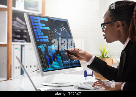 Close-up Of A Businesswoman's Hand Analyzing Graph On Computer At Workplace - Stock Image