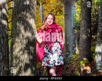 Nature-lover teen girl countrygirl in woodland forest amongst trees wearing red scarf and short skirt mini miniskirt happy laughing - Stock Image