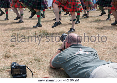 Photographer gets a low angle shot of marching bagpiper's legs  and kilt hems. - Stock Image