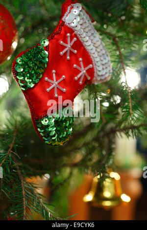 A small decorated Christmas stocking is hanging on the Christmas tree. - Stock Image