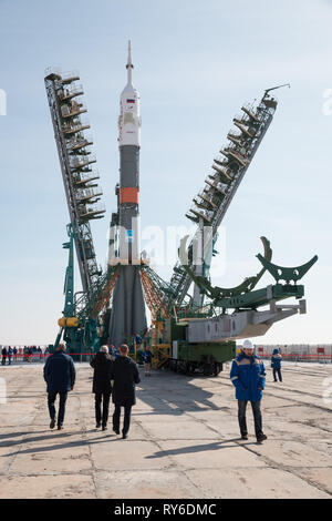 Baikonur, Kazakhstan. 12th Mar, 2019. The Russian Soyuz MS-12 rocket is raised into a vertical position and the gantry arms closed on the launch pad at the Baikonur Cosmodrome March 12, 2019 in Baikonur, Kazakhstan. The Expedition 59 crew: Nick Hague and Christina Koch of NASA and Alexey Ovchinin of Roscosmos will launch March 14th for a six-and-a-half month mission on the International Space Station. Credit: Planetpix/Alamy Live News - Stock Image