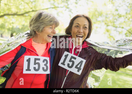 Happy active senior women finishing sports race, wrapped in thermal blanket - Stock Image