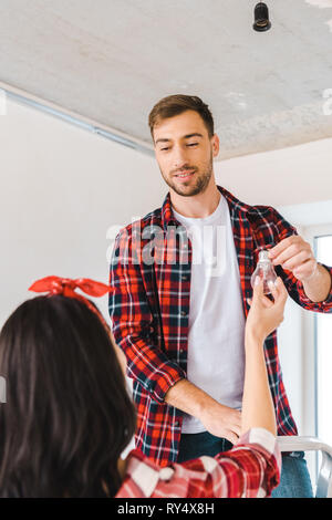 handsome man standing on ladder and taking light bulb while looking at girlfriend - Stock Image