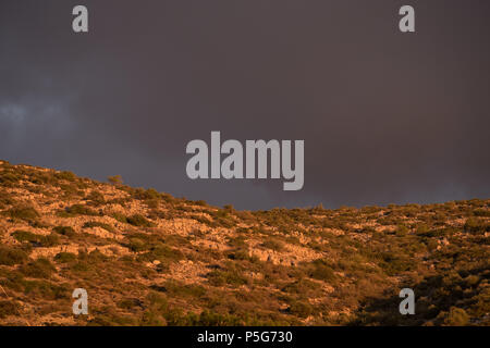 Greek mountain, Golden Hour Beautiful Light with Grey Dramatic Clouds, Saronida, Greece. - Stock Image