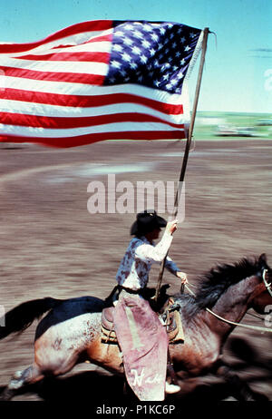 Cowboy riding on a horse flying the American flag during a rodeo stampede show in Stapleton Ohio - Stock Image