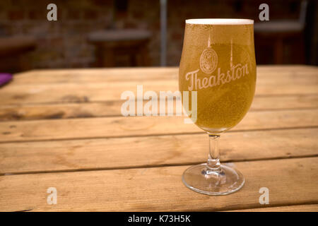Half pint of Theakston's ale in a stemmed glass on a wooden table, Yorkshire, United Kingdom - Stock Image