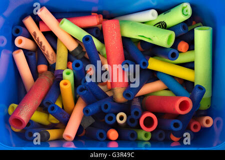Foam toy Nerf gun darts in multiple colors in a blue box. - Stock Image