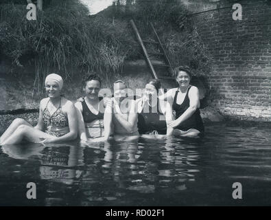 c 1940, historical, ladies in their swimming costumes having fun bathing in a part of a river by a bridge, England, UK - Stock Image