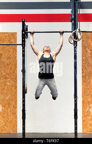 Young fit strong muscular girl athlete doing pull-ups on a bar during her workout in a full frontal view inside a professional gym - Stock Image