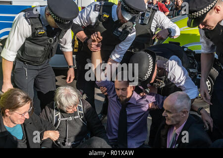 LLondon, UK. 31st October 2018.  Most people at Extinction Rebellion's Declaration of Rebellion left the road they were blocking in front of parliament after a closing address by George Monbiot, but several small groups decided to remain on the road, including Donnachadh McCarthy and George Monbiot. Police immediately warned them they would be arrested if they did not move, and begin to lift one of the  protesters. By the time I left around 15 arrests had been made, including of McCarthy, while some others agreed to leave the road. Peter Marshall/Alamy Live News - Stock Image