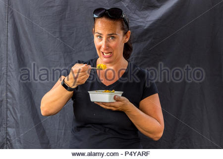 A female stallholder sampling the product, paella at the Fleet Food Festiva against a black backdrop. - Stock Image