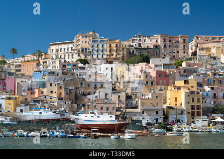 Fishing trawlers being repaired in dry dock at Sciacca Port with the town behind, south coast of Sicily, Italy - Stock Image