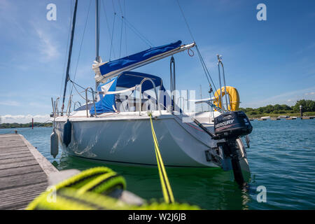 Sailing boat with outboard engine moored on a pontoon jetty - Stock Image