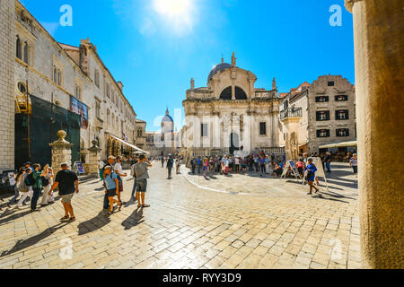 Tourists walk under the hot summer sun in the stradun or placa in Old Town Dubrovnik with St Blaise Church and the Dubrovnik Cathedral in view - Stock Image