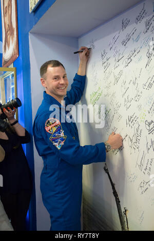 International Space Station Expedition 59 crew member Nick Hague of NASA signs a wall mural bearing the names of those who have flown in space at the Baikonur Cosmodrome March 10, 2019 in Baikonur, Kazakhstan. Expedition 59 crew: Christina Koch of NASA, Alexey Ovchinin of Roscosmos, and Nick Hague of NASA will launch March 14th onboard the Soyuz MS-12 spacecraft for a six-and-a-half month mission on the International Space Station. - Stock Image