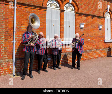 Elderly musicians from the Belmond Venice Simplon Orient Express in striped blazers entertain and perform at Folkestone West railway station, Kent - Stock Image