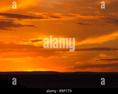 Orange sunset with clouds over ocean at Penneshaw on Kangaroo Island in South Australia, Australia. - Stock Image