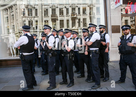 Oxford Circus, London, UK. 19th Apr, 2019. A large number of police presence in Oxford Circus as they prepare to remove environmental activists from Extinction Rebellion movement group from the site. According to the Met Police, nearly 700 activists have been arrested since the demonstration started on 11 April 2019. Credit: Dinendra Haria/Alamy Live News - Stock Image