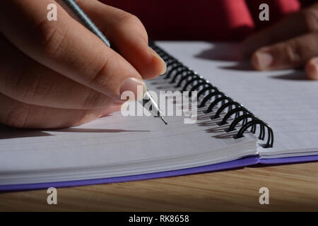 Millennial woman writing in a spiral bound notebook, pen in hand - Stock Image