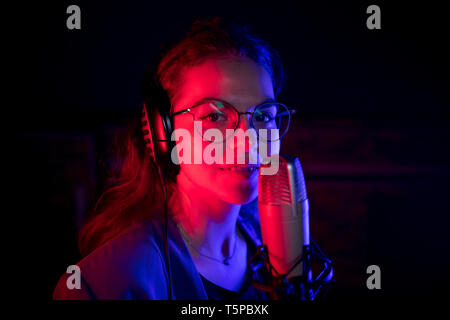A young woman in glasses singing by the microphone in neon lighting and looking in the camera - Stock Image