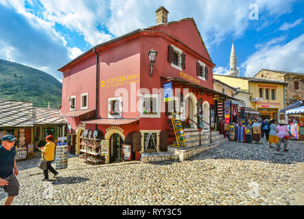 Tourists shop for gifts and souvenirs and wander Mostar, Bosnia's old town with a minaret in the background - Stock Image