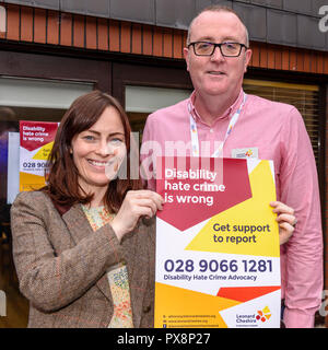 Belfast, Northern Ireland. 16/10/2016 - Terry McCorry, Disability Hate Crime Advocate for Leonard Cheshire NI with SDLP's Nichola Mallon hold up an awareness poster for Disability Hate Crime support during Hate Crime Awareness Week. - Stock Image
