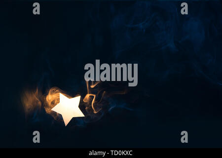 Star flare, a shining star from paper on a dark background with gradient warm and cold smoke. Celebration concept with copy space - Stock Image