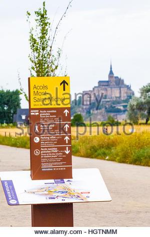 Visitor Sign showing the way to (or Acces) to Mont Saint Michel,(along with a map) & Mont St Michel in Normandy, - Stock Image