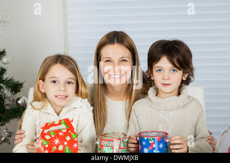 Happy Mother And Children With Christmas Gifts - Stock Image