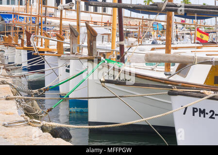 A row of yachts are secured to a mooring with ropes in a marina in Port de Pollenca, Mallorca, Spain. - Stock Image