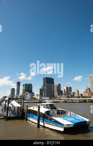 BRISBANE, Australia - A Citycat ferry pulled up to a ferry terminal at South Bank, with the Brisbane city skyline - Stock Image