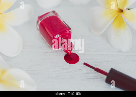 red nail polish bottle spilling color on wooden surface with flowers around it, concept of cosmetics industry and manicure - Stock Image