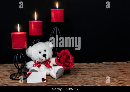 Cudlely teddy bear with red bow tie, red rose, red candles perched on black candle holders on mesh place mat and wooden table with card and dark back - Stock Image