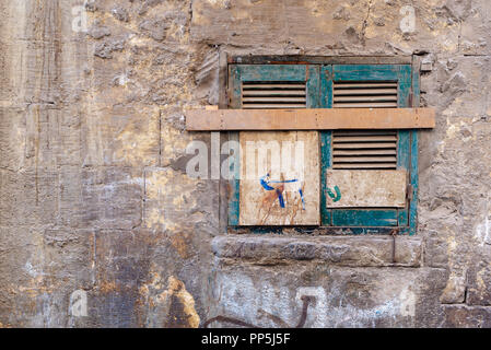 Old grunge window with closed green broken shutters on dirty cracked bricks stone wall - Stock Image