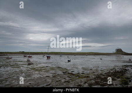 The Ouse with anchored boats at low tide from Willy Pots Rock on Holy Island with Lindesfarne Castle under renovation England UK - Stock Image