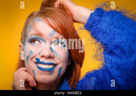 Happy, pretty, redheaded, young woman wearing a fuzzy blue jumper, with crazy blue make-up, smiling © Jeremy - Stock Image