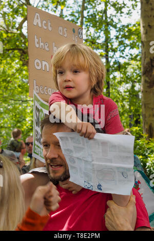 London, UK. 12th May 2019. A child on his father's shoulders waits for the start of the march by several thousand mothers, children and some fathers behind 11-year-olds and 3 giant push chairs with stilt walkers from Hyde Park Corner to a rally filling Parliament Square, backing Extinction Rebellion's call for the drastic and urgent action needed to avert the worst consequences of climate change, including possible human extinction. Our politicians have declared a climate emergency but now need to take real action rather than continuing business as usual which is destroying life on our planet. - Stock Image