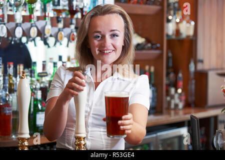 Female Bartender Serving Beer Behind Counter - Stock Image