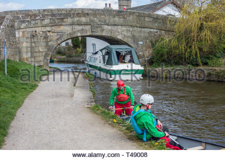 Canoeists pull into the bank as a pleasure boat passes on the Lancaster Canal at Hest Bank, Lancashire, England, UK. - Stock Image
