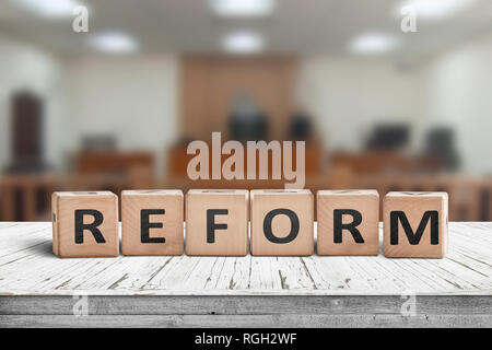 Reform sign on a desk with a blurry background of a court room - Stock Image